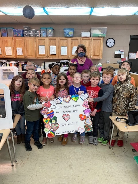Mrs. Melton's First Grade Class holding a sign which shows appreciation to our school board members.